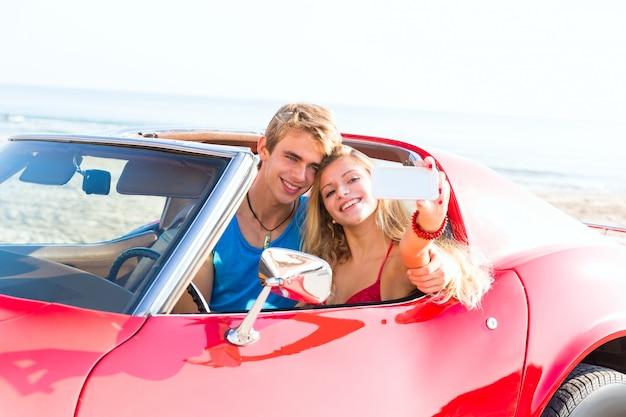Photo selfie d'un jeune couple adolescent en décapotable Photo Premium