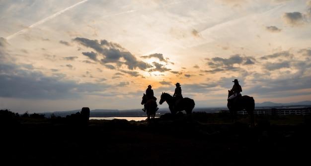 Photo de silhouette de femmes montées à cheval au coucher du soleil pour une activité Photo Premium