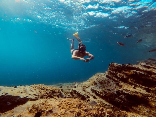 Photo sous-marine d'hommes plongeurs plongeant en apnée dans l'eau de mer Photo Premium