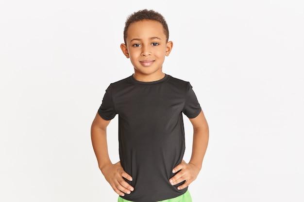 Photo De Studio De Beau Petit Garçon Athlétique à La Peau Sombre Posant Isolé En T-shirt Noir En Gardant Les Mains Sur Sa Taille, S'entraînant à L'intérieur. Photo gratuit