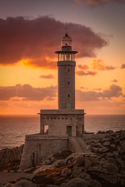 Photo Verticale Du Phare De Punta Nariga Entouré Par La Mer Pendant Le Coucher Du Soleil En Espagne Photo gratuit