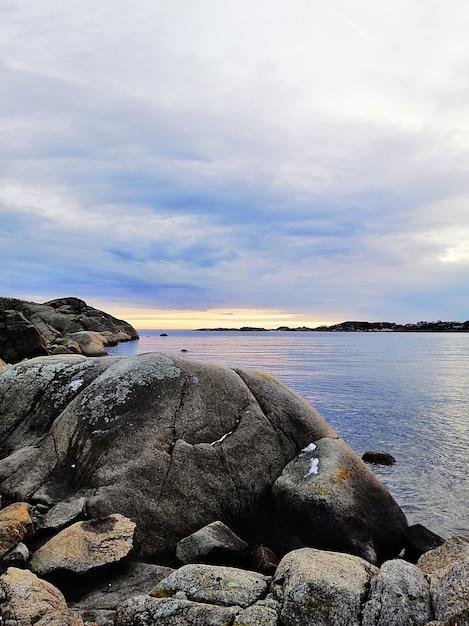 Photo Verticale De La Mer Entourée De Rochers Sous Un Ciel Nuageux Pendant Le Coucher Du Soleil En Norvège Photo gratuit