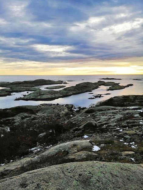 Photo Verticale De Roches Entourées Par La Mer Pendant Le Coucher Du Soleil à Rakke En Norvège Photo gratuit