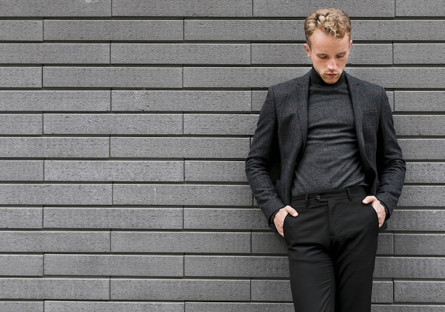 Photogénique jeune homme appuyé contre le mur Photo gratuit