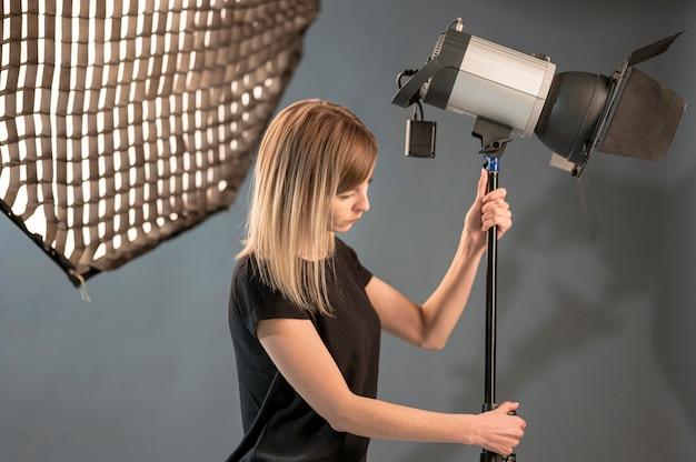 Photographe Ajustant La Lampe De Studio Photo gratuit
