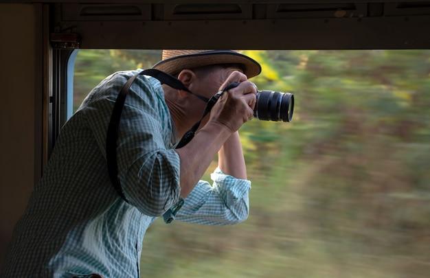 Photographe asiatique portant un chapeau avec caméra, prenez des photos de la fenêtre ouverte du train vintage Photo Premium