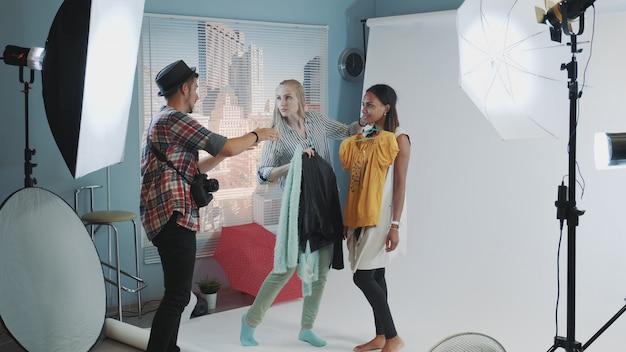 Photographe Avec Assistant Choisissant Des Vêtements Pour La Prise De Vue Du Modèle Photo Premium