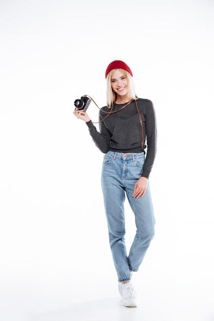 Photographe Femme Décontractée Souriante Debout Et Tenant Une Caméra Rétro Photo gratuit