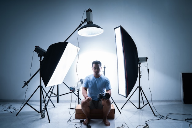 Photographe Masculin En Studio De Photographie Entouré De Matériel D'éclairage Photo Premium