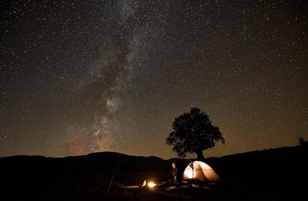 Photographe Touristique Au Feu De Camp Devant La Tente, Appareil Photo Sur Trépied Sous Un Ciel étoilé Sombre. Photo Premium