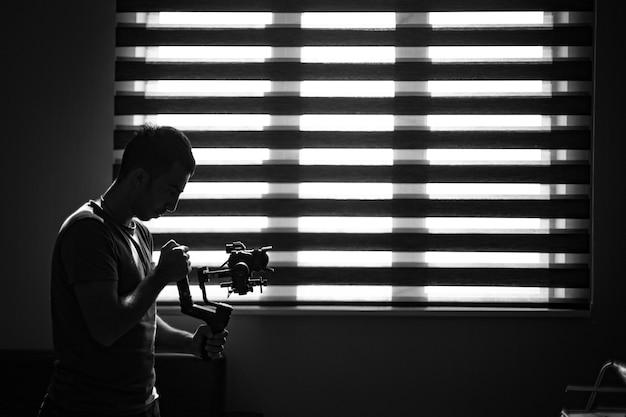 Photographe Vérifiant Son Appareil Photo Dans L'obscurité Photo gratuit