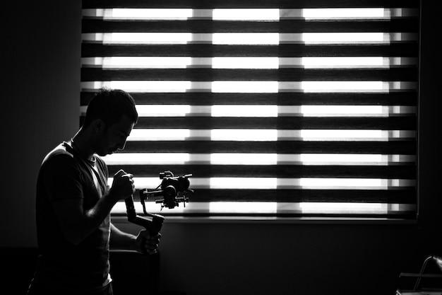 Photographe Vérifiant Son Appareil Photo Dans L'obscurité. Photo gratuit