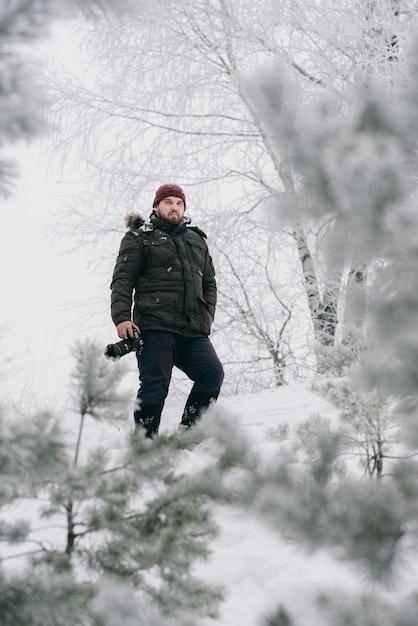 Photographe voyageur prenant des photos dans la forêt d'hiver Photo Premium