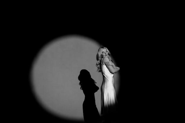 Photographier avec des projecteurs, noir et blanc, lumière et obscurité, avec la silhouette d'une belle fille posant, tonifiant à la mode. Photo Premium