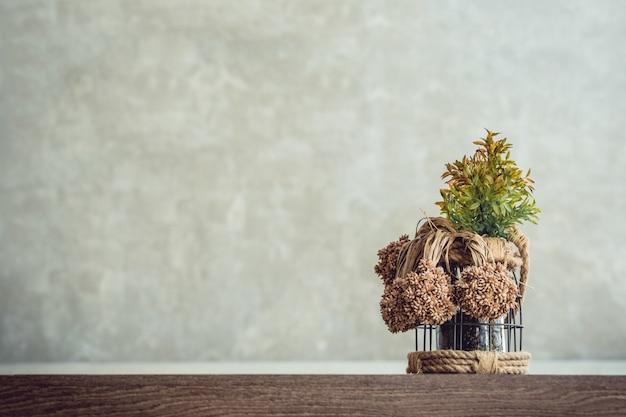 Photos de l'avant d'un pot de plantes ornementales posé sur une table en bois avec un fond de mur de ciment Photo Premium