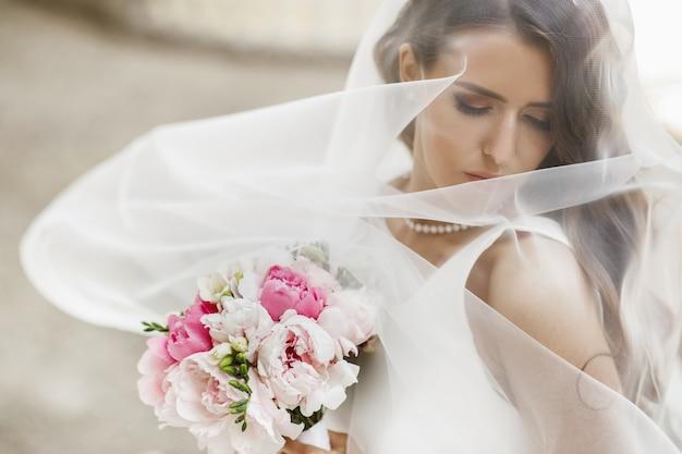 Photos de la mariée magnifique posant sous le voile à l'extérieur Photo gratuit