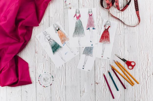 Photos Avec Des Modèles De Robe, Tissu Rose Et D'autres Accessoires Pour L'artisanat Se Trouvent Sur La Table Photo Premium