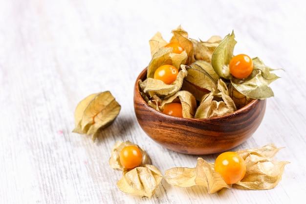Physalis sur un plat d'argile. baies mûres de physalis automne Photo Premium