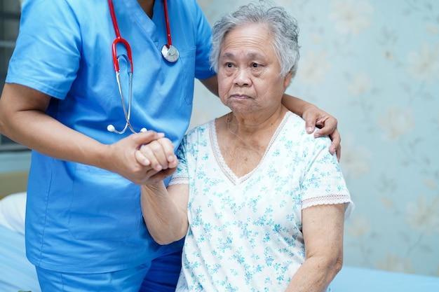 Un physiothérapeute asiatique aide et soutient un patient âgé à l'hôpital. Photo Premium