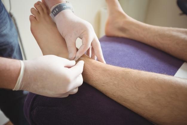 Physiothérapeute Effectuant Des Aiguilles Sèches Sur La Jambe D'un Patient Photo gratuit