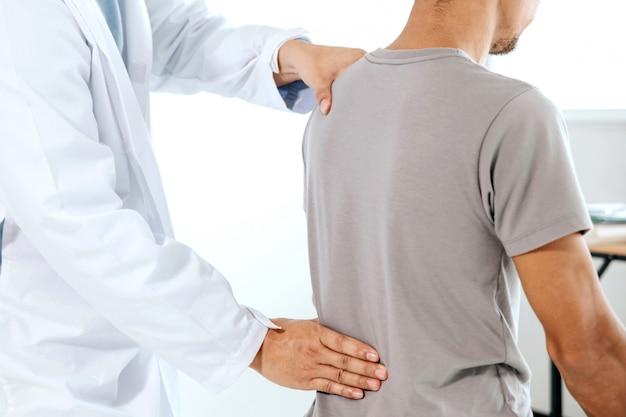 Physiothérapeute effectuant un traitement de guérison sur le dos de l'homme. patient souffrant de douleurs dorsales, massothérapeute Photo Premium