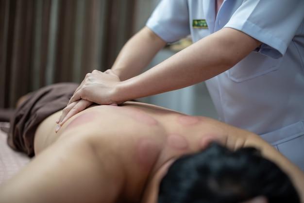 Le physiothérapeute vérifie les anomalies du corps après le traitement par ventouses. Photo Premium