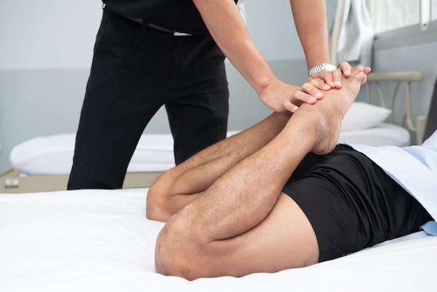 Les physiothérapeutes utilisent les poignées de la jambe du patient pour s'allonger sur le lit dans une salle médicale. Photo Premium