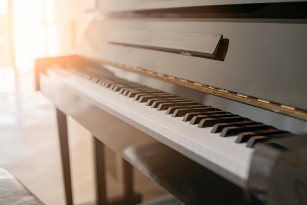 Piano brillant noir avec la lumière du soleil de la fenêtre de rideau blanc Photo Premium