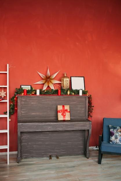 Piano et décor de noël sur fond de mur rouge Photo Premium