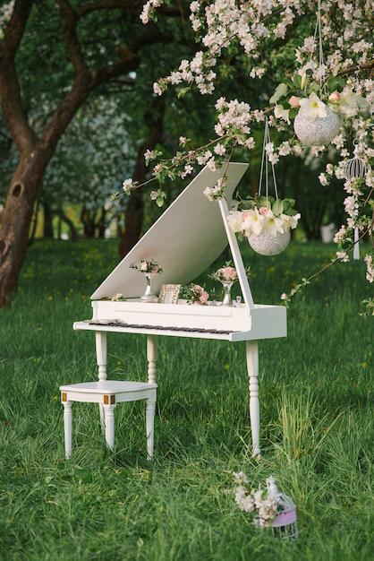 Un piano à queue blanc se dresse au printemps dans les vergers de pommiers en fleurs. décor de mariage ou d'anniversaire romantique et délicat Photo Premium