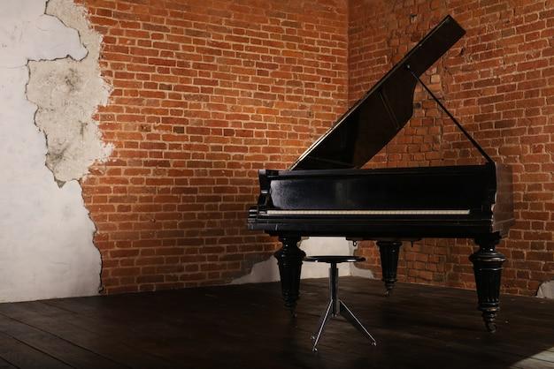 Piano à Queue Avec Couvercle Surélevé Et Tabouret Près Du Mur De Briques Photo Premium