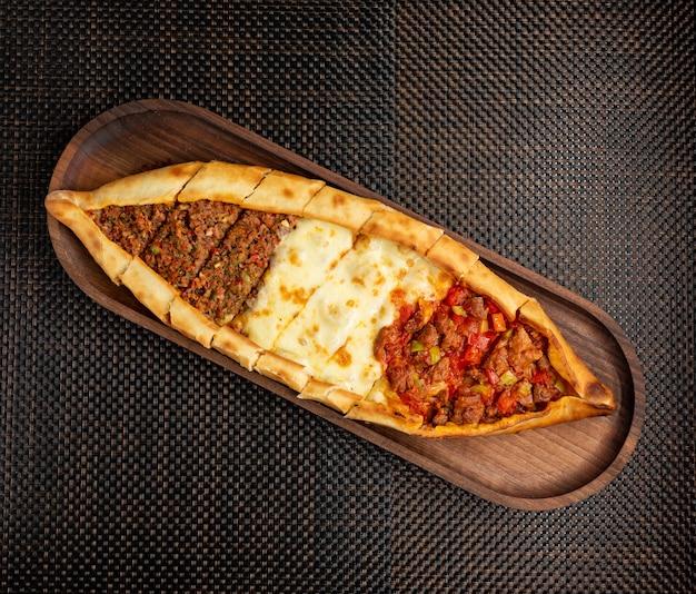 Pide Avec Du Fromage De Viande Farci Et Des Morceaux De Viande Frite Sur Un Bol En Bois Photo gratuit