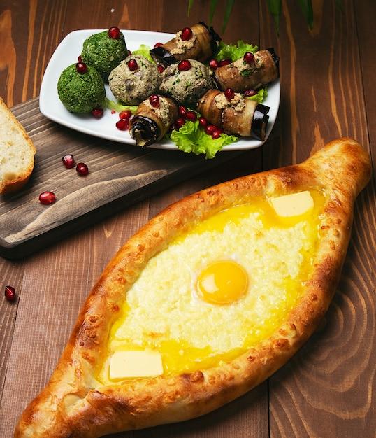 Pide de plat traditionnel turc cuit au four. pizza turque au fromage et oeuf avec salade de légumes. Photo gratuit