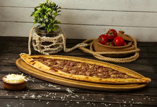 Pide Traditionnel Turc Avec Du Fromage Et De La Viande Farcie Sur Une Planche De Bois Photo gratuit