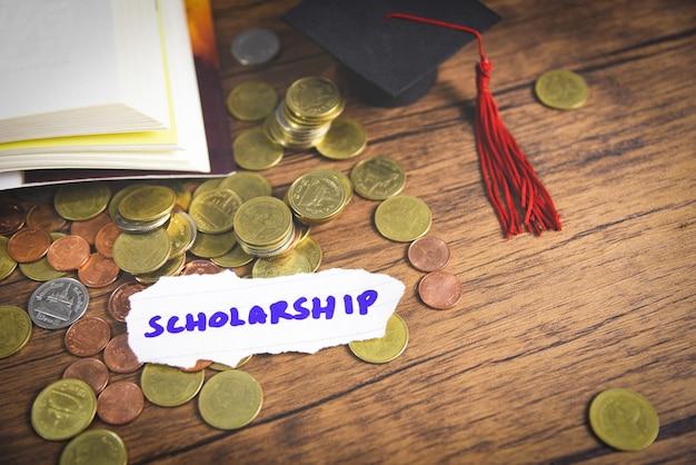 Pièce d'argent sur bois avec fond sombre et graduation cap sur livre ouvert Photo Premium