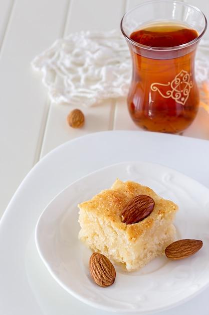 Pièce basbousa traditionnel arabe gâteau de semoule aux noix eau de fleur d'oranger vertical espace de copie fond blanc Photo Premium