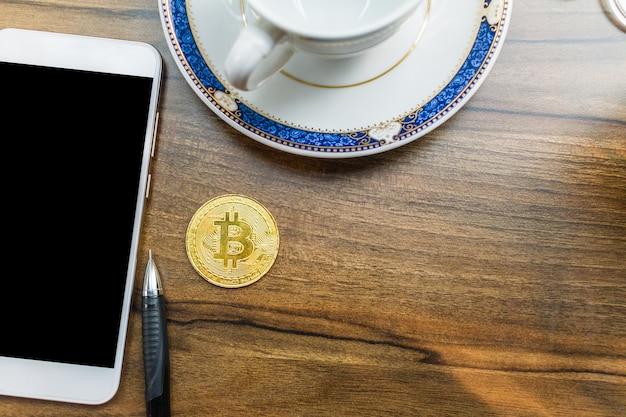 Pièce de bitcoin sur smartphone Photo Premium