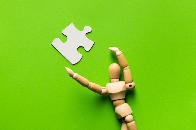 Pièce de puzzle blanche et figure humaine en bois sur une surface verte Photo gratuit