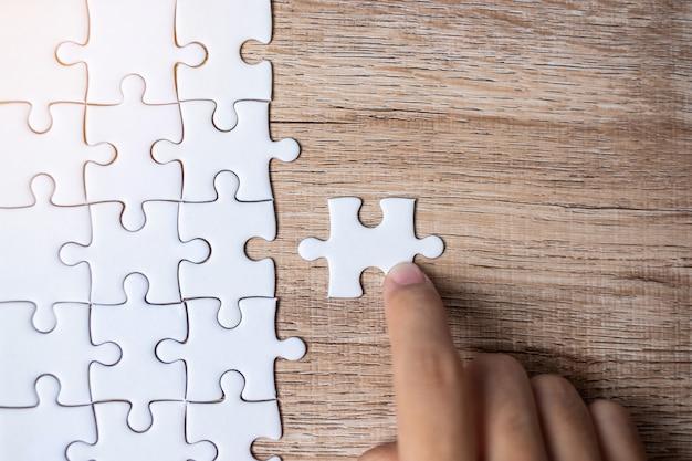 Pièce de puzzle reliant la main d'homme d'affaires. solutions d'entreprise, objectif de la mission, succès, objectifs, coopération, partenariat et stratégie Photo Premium