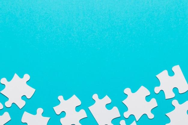 Pièce de puzzle séparée au bas de l'arrière-plan bleu Photo gratuit