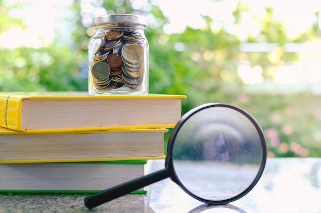 Pièces d'argent dans le bocal en verre sur les livres et la loupe Photo Premium