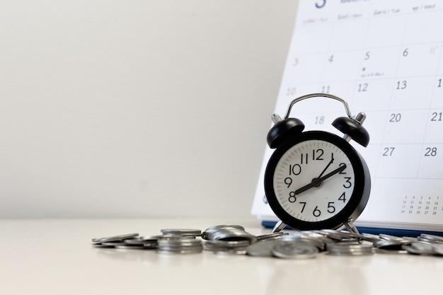 Les pièces d'argent étape avec calendrier et réveil copier l'espace pour le texte Photo Premium