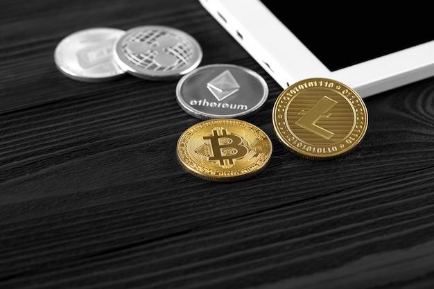 Pièces d'argent et d'or avec bitcoin, ondulation et symbole ethereum sur fond de bois. Photo Premium