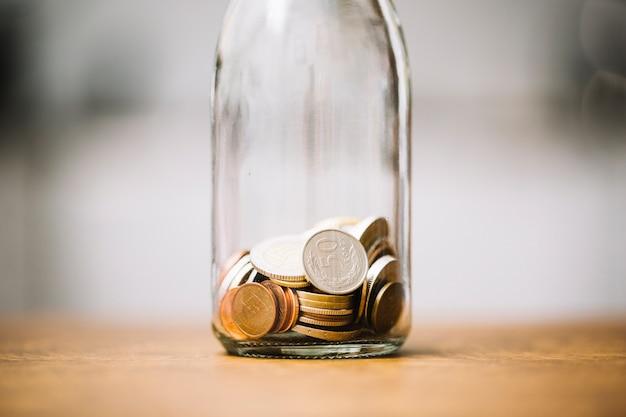 Pièces dans la bouteille en verre sur la surface en bois Photo gratuit