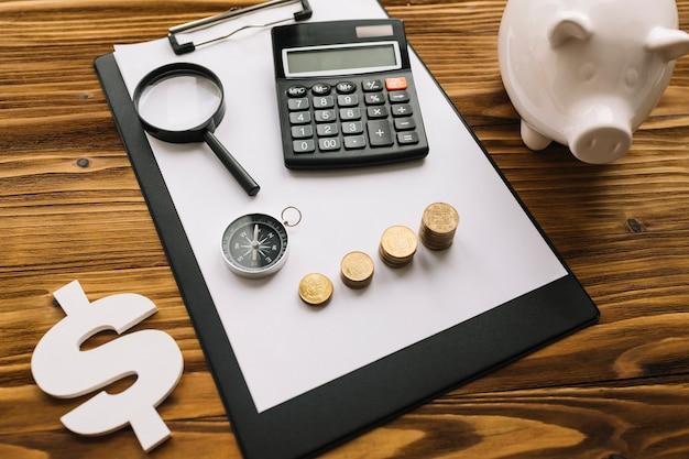 Pièces empilées; boussole; loupe et calculatrice sur presse-papiers avec signe dollar et tirelire Photo gratuit