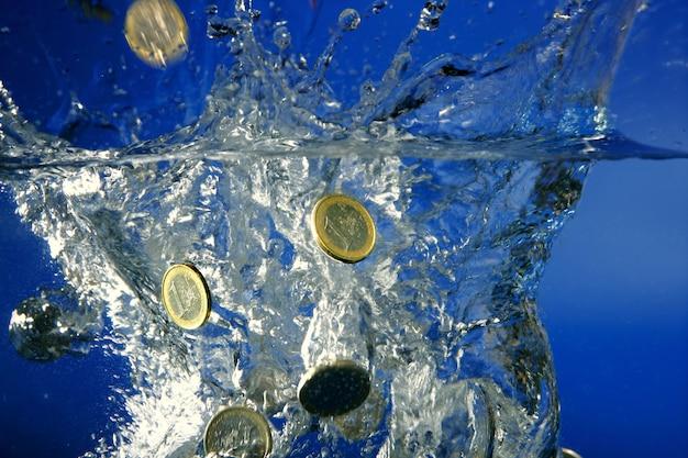 Les pièces en euros tombent dans l'eau Photo Premium