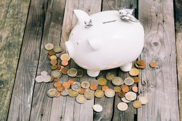 Pièces de monnaie autour de la tirelire blanche sur une vieille table en bois Photo gratuit