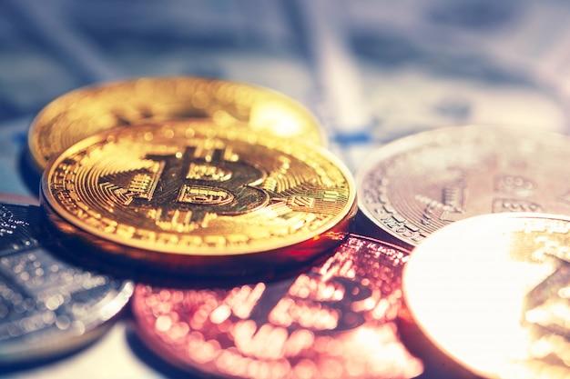 Pièces de monnaie bitcoin d'or sur une monnaie de papier dollars Photo Premium