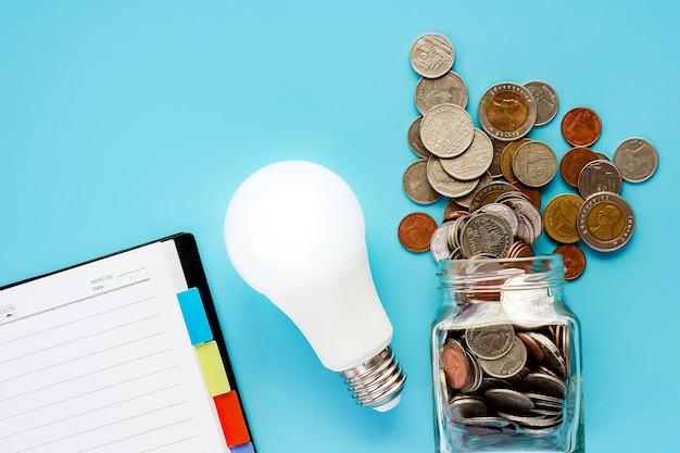 Pièces de monnaie dans un bocal en verre et à l'extérieur avec ampoule led rougeoyante et cahier vierge au dos bleu Photo Premium