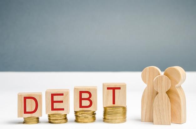 Pièces de monnaie en hausse, blocs de bois avec le mot dette et famille. difficultés financières. Photo Premium